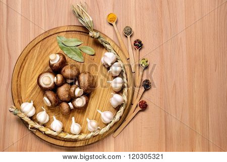 Garlic, mushrooms and spice on wooden table.