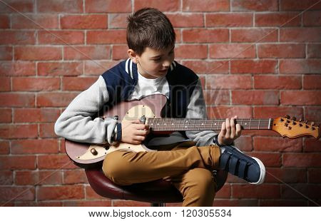 Cute little boy playing guitar on brick wall background