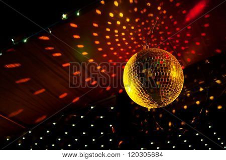Mirror disco ball with light reflection on the ceiling on a black background ** Note: Visible grain at 100%, best at smaller sizes