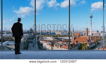 Business man in a loft looking at skyline of Berlin in Germany (3D Rendering)