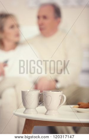Two cups of tea with cookies on the table and mature couple on background