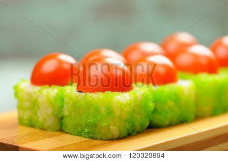 Tasty Japanese Fantasy Rolls With Cherry Tomatoes And Green Caviar Served On Bamboo Plate