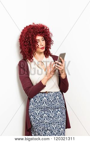 Young curly redhead businesswoman with smartphone