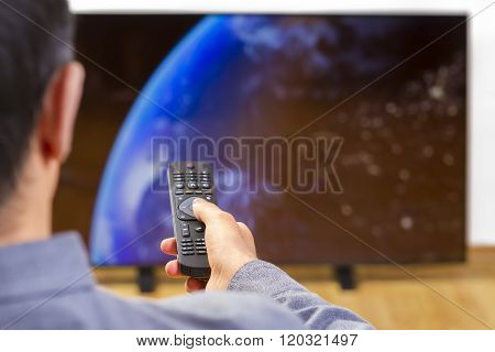 Man with Remote Conrol Watching Tv