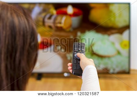 Over the shoulder view of girl sitting on sofa holding tv remote and surfing programs on television. Focus on the remote control.