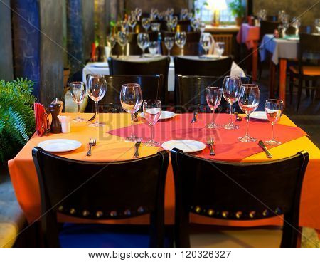 Served table in restaurant. silverware, crockery and kitchen utensils on red orange napkins. Classic