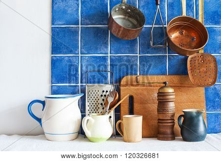 Kitchenware utensils. colored pots jugs pans, cutting board, wooden spoon, cooper ladle stewpan. blu