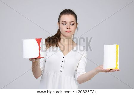 girl in white dress holding paint cans