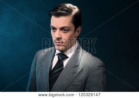 Retro 1940S Business Man In Suit And Tie Against Blue Wall.