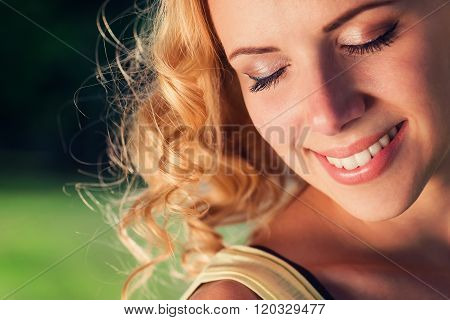 Blond woman with curly hair, closed eyes. Green nature.