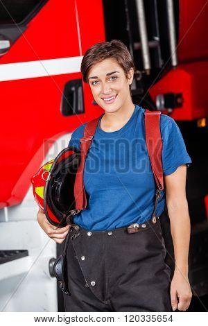 Happy Firefighter Holding Helmet Against Firetruck