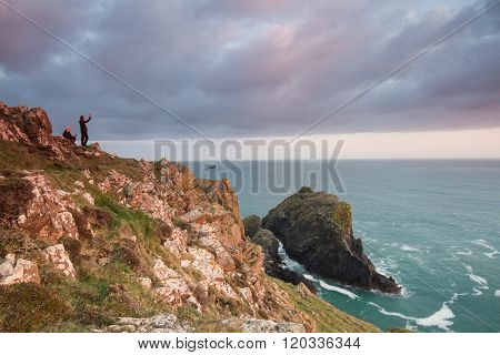 KYNANCE COVE, CORNWALL, UK - CIRCA JULY 2015. Two people taking selfies on the side of a cliff whilst enjoying the seascape of Kynance Cove in Cornwall, England.