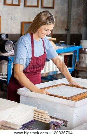 Female Worker Dipping Mold In Pulp And Water Mixture