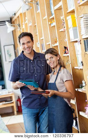 Smiling Saleswoman Showing Books To Male Customer