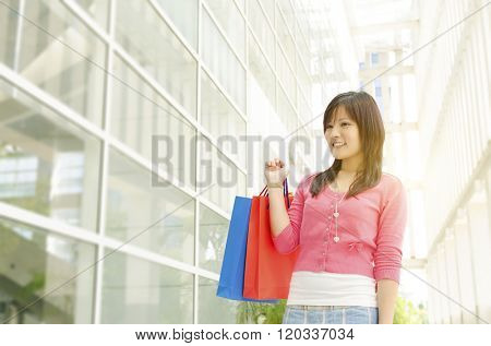 Young Asian woman with shopping bags walking out from shop at the mall. Beautiful golden sunlight at background.