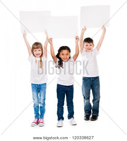 three cheeerful children holding en empty paper sheet above themselves isolated on white background