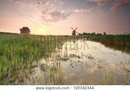Charming Dutch Windmill By River At Sunrise