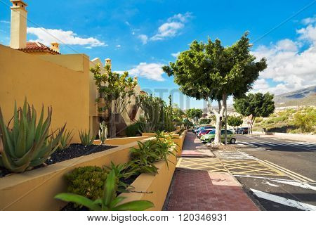TENERIFE ISLAND, SPAIN - OCTOBER 28, 2015 : Street with typical Canary style holiday apartments in Costa Adeje, Tenerife, Canary Islands