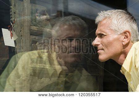 Man looking at dresser in shop window