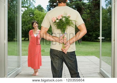 Man surprising wife with flowers