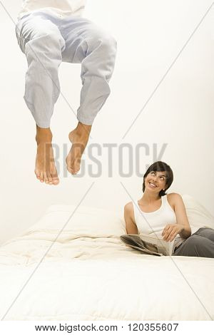 Woman watching husband jump on bed