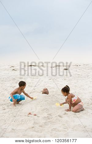 Children burying father in sand