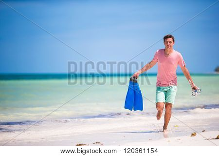 Young man with mask and fins. Holiday vacation on a tropical beach.