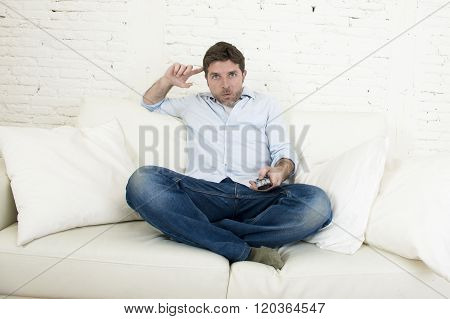 young man watching tv sitting at home living room sofa with remote control looking relaxed enjoying television program or movie in disbelief and shock face expression