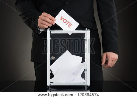 Male Hand Putting Vote Into A Ballot Box