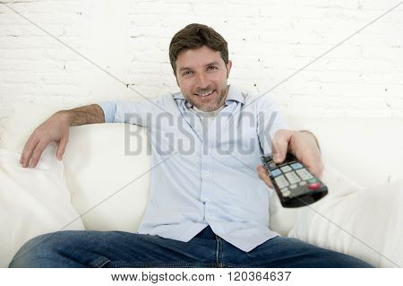 young happy man watching tv sitting at home living room sofa with remote control looking relaxed enjoying television program or movie