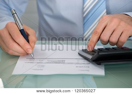 Businessman Calculating Invoice With Calculator