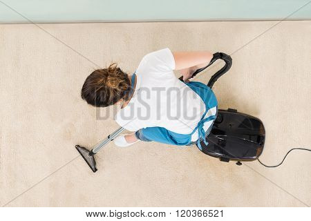 Young Female Janitor Vacuuming Floor