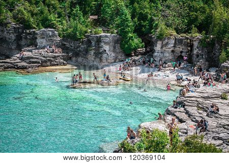 Amazing natural rocky beach and tranquil azure clear water with people swimming in the lake