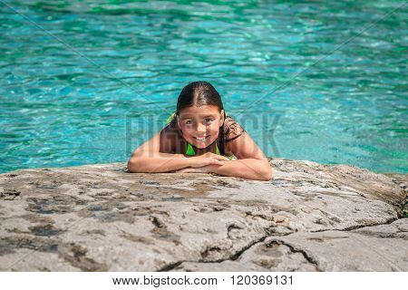 Joyful child girl lying and relaxing on the edge of the cliff against gorgeous amazing Cyprus lake