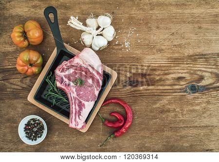Raw fresh meat ribeye steak with pepper, salt, chili, garlic, heirloom tomatoes and rosemary in cook