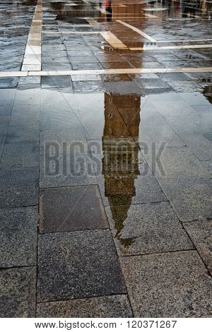 Saint Mark campanile or bell tower reflected on the wet stone pavement of the famous square in Venice, Italy