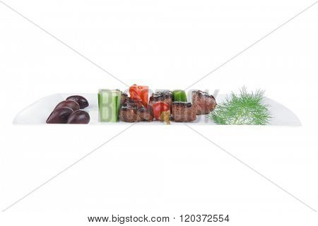 european food: roast beef meat goulash over white plate isolated on white background with tomatoes and dill