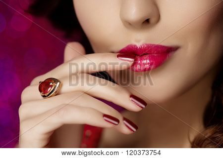 Red woman lips close up. Beautiful model girl with lipstick, manicure with nail polish Products Treatment