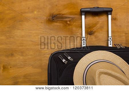 Black Traveler Suitcase And A Straw Hat