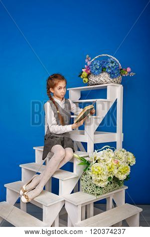 Teenage Girl In School Uniform Reading Book.