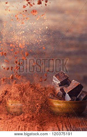 Falling cocoa powder on a wooden table