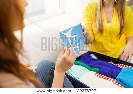 tourism, vacation, luggage and people concept - close up of women with airplane tickets and clothes in travel bag at home