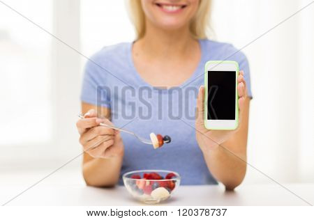 healthy eating, dieting, technology, food and people concept - close up of young woman with smartphone eating fruit salad at home