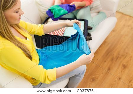 trip, vacation, luggage and people concept - close up of happy young woman or teenage girl packing clothes into travel bag
