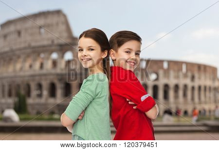 childhood, travel, tourism and people concept - happy smiling boy and girl standing back to back over coliseum in rome