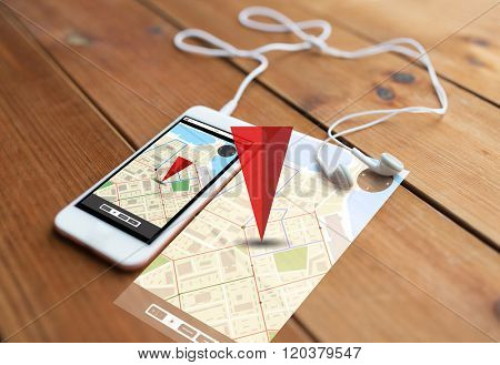 technology, navigation, gadget and object concept - close up of white smartphone and earphones on wooden surface with gps navigator map on screen