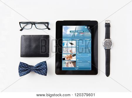 media and business concept - tablet pc computer with news web page, wallet, eyeglasses, bowtie and wristwatch on table