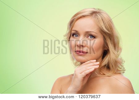 beauty, people and skincare concept - smiling woman with bare shoulders touching face over green natural background