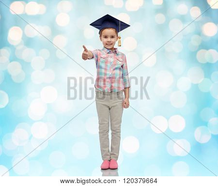 childhood, school, education, learning and people concept - happy girl with in bachelor hat or mortarboard showing thumbs up over blue holidays lights background