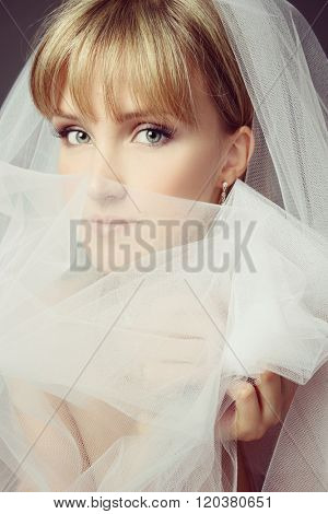 Vintage style portrait of young beautiful thoughtful bride with bridal veil